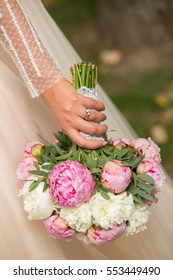 Beautiful wedding bouquet in hands of the bride, focus on hand