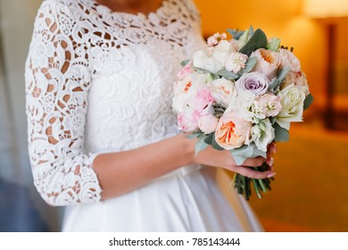 Beautiful wedding bouquet in hands of the bride. Trendy and modern wedding flowers. Peonies and roses. Woman in wedding dress in hotel room. Blurred background.