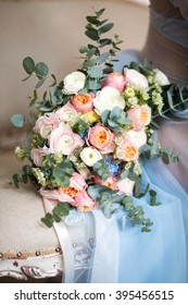 Beautiful wedding bouquet lies on vintage beige chair.  Bouquet consists of pink and white roses, eucalyptus.