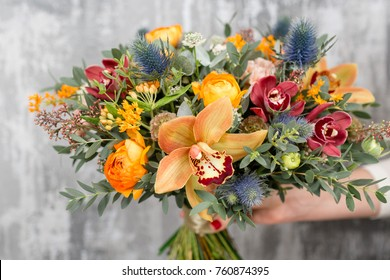 beautiful wedding bouquet of mixed flowers in woman hand. the work of the florist at a flower shop