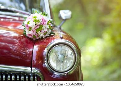 Beautiful wedding bouquet on vintage wedding car