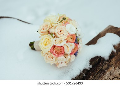 beautiful wedding bouquet with ribbons lies in the woods near a tree in the winter