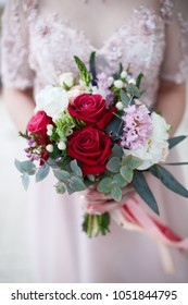 Beautiful wedding bouquet with roses in brides hands