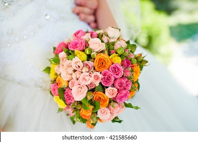 Beautiful wedding bouquet of roses in hands of the bride