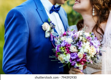 beautiful wedding bouquet with ultra violet and white flowers in the hands of the bride and groom in a blue suit