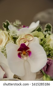beautiful wedding bouquet with white orchids and golden weddingrings