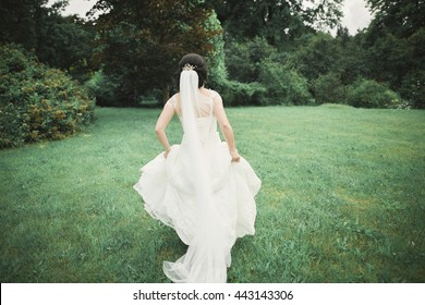 Beautiful wedding bride running in the garden