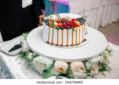 A beautiful wedding cake, decorated with fruits, raspberries, strawberries and blueberries. The bottom of the cake is decorated with rose flowers. Confectionery on the table. Holiday concept