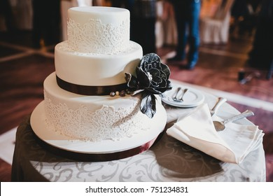 Beautiful wedding cake decorated with laces and black flower