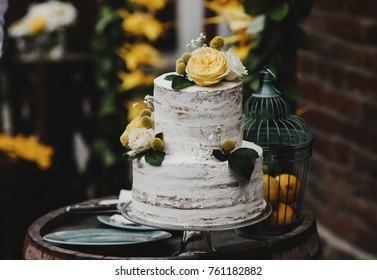 Beautiful wedding cake decorated with yellow flowers and greenery