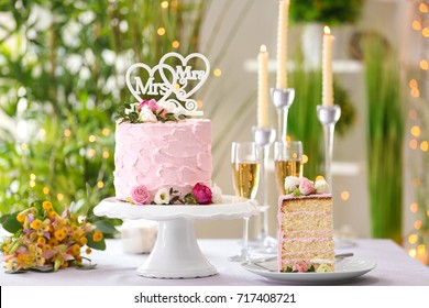 Beautiful wedding cake for lesbian wedding decorated with flowers on table
