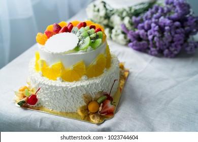 beautiful wedding cake with strawberry , kiwi and orange on the table decorated wih flower