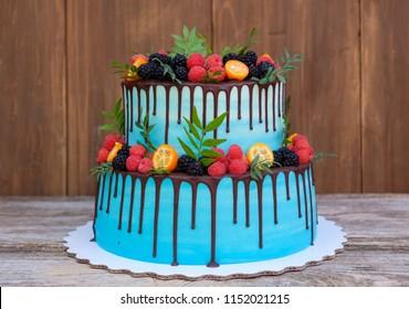 beautiful wedding cake in two tiers, decorated with fresh raspberries, blackberries, blueberries, chocolate icing
