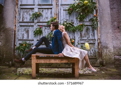 Beautiful wedding casual couple in love on the decorated wooden wall of facrory