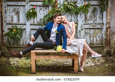 Beautiful wedding casual couple in lovelooking forvard on the decorated wooden wall of facrory