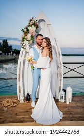 a beautiful wedding ceremony by the water on the dock. Romantic wedding in the sea style in a yacht club. Beautiful bride with long curls in an elegant white dress and the groom in the blue suit.