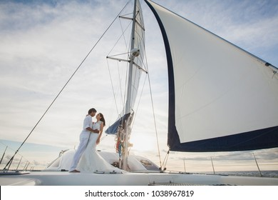 Beautiful wedding couple bride and groom on yacht at wedding day outdoors in the sea. Happy marriage couple kissing on boat in ocean. Stylish Marine wedding.