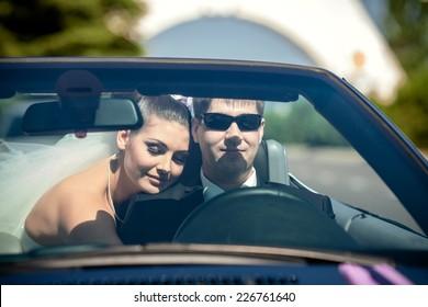 Beautiful wedding couple in car