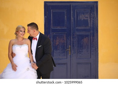 Beautiful wedding couple embrancing,  blue door at the background