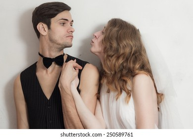 Beautiful wedding couple fool around. Standing beside on white wall background.
