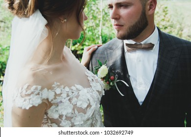 Beautiful wedding couple in the forest. The bride in tulle veil is hugging bearded groom in bow tie. Wedding buttonhole and checkered suit in Great Gatsby style. Stylish and rustic love story.