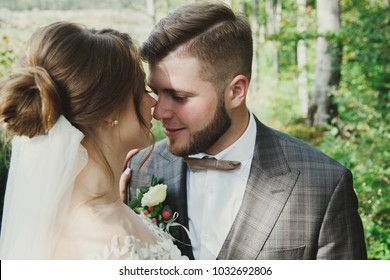 Beautiful wedding couple in the forest. The bride in tulle veil is kissing bearded groom in bow tie. Wedding buttonhole and checkered suit in Great Gatsby style. Stylish and rustic love story.