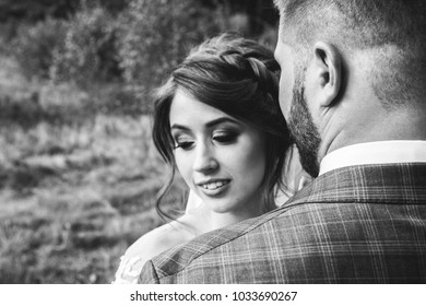 Beautiful wedding couple in the forest. The bride in tulle veil turns her head to the side near the bearded groom in checkered suit. Black and white love story. Amazing bridal portrait.