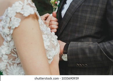Beautiful wedding couple in the forest. The bride with tulle veil and open low back elegant dress is touching the groom in bow tie. Wedding buttonhole and checkered suit in Great Gatsby style.