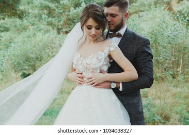 Beautiful wedding couple in the forest. The bride in tulle veil and elegant dress with flowers is hugging the groom in bow tie. Hipster rustic stylish love story outdoors.