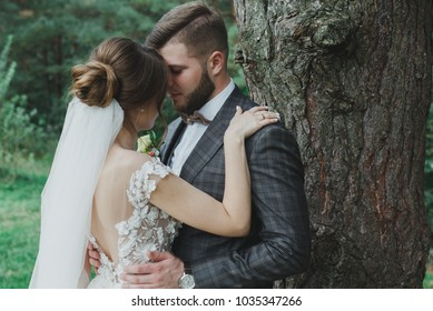 Beautiful wedding couple in the forest. The bride with tulle veil and open low back elegant dress is hugging the groom in bow tie. Wedding buttonhole and checkered suit in Great Gatsby style. Bride.