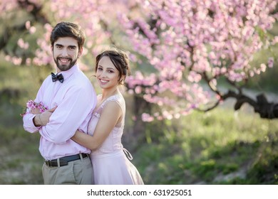 Beautiful wedding couple in the gardens of a blossoming peach