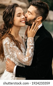 Beautiful wedding couple laugh and kiss on the background of stones. High quality photo