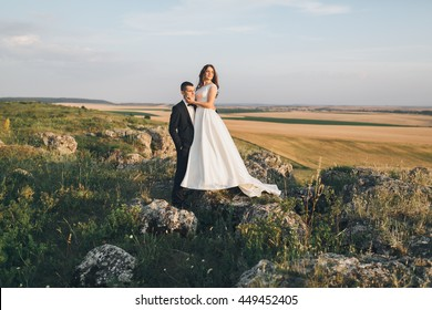 Beautiful wedding couple, love on the sunset. Bride and groom posing on the nature.
