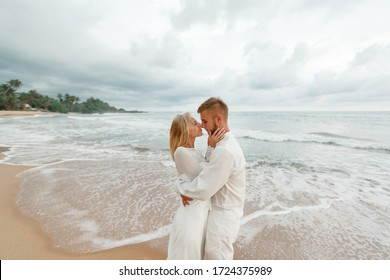 Beautiful wedding couple near the sea. Young couple having tender moments and kissing on the beach at sunset. Man flirting with his woman on romantic holidays in summer time . Love concept