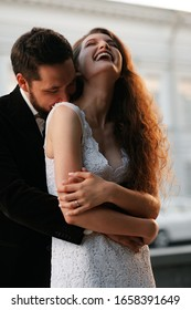 Beautiful wedding couple of newlyweds - red-haired young bride in a white dress and a bearded groom in a black suit. Amazing smiling wedding couple. Pretty bride and stylish groom.