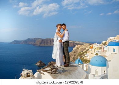 Beautiful wedding couple on a background of white architecture and sea on Santorini island, Greece