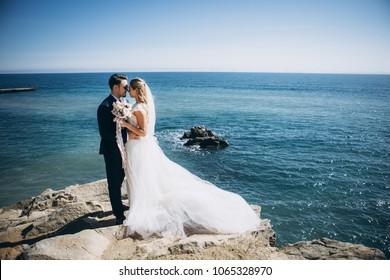 Beautiful wedding couple on their wedding photoshoot by the sea