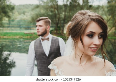 Beautiful wedding couple on the wooden bridge near the river. The bride with elegant hairdo are walking to her bearded groom in bow tie. Rustic outdoors details portrait photo. Happy bride and groom.