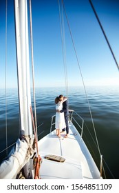 Beautiful wedding couple on yacht at wedding day outdoors in the sea. Beautiful elegant  bride in a white dress and stylish groom on the luxury yacht sailing down the sea. Together. Wedding day.
