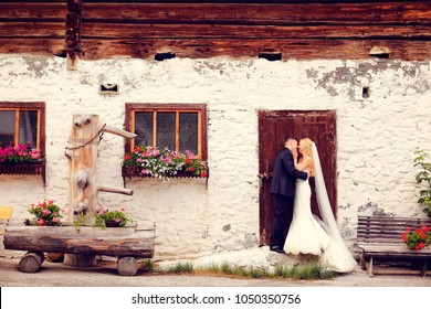 Beautiful wedding couple posing in front of old rustic house