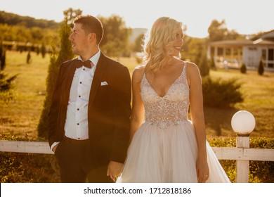 Beautiful wedding couple posing outdoor on golden hour