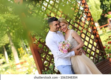 beautiful wedding couple posing in park on sunny day