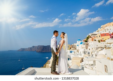 Beautiful wedding couple in Santorini, Greece. Hold hands against the sea