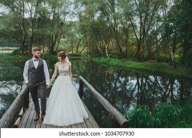 Beautiful wedding couple is standing on the wooden bridge. The bride in tulle veil and elegant hairdo is holding hands with her bearded groom in bow tie. Rustic outdoors stylish love story.