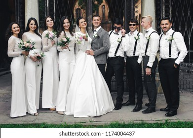 Beautiful wedding couple stands with friends before black steel gates