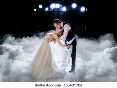 Beautiful wedding couple stands in the smoke during their first dance
