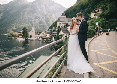 A beautiful wedding couple walks on the lake and mountains background in a fairy Austrian town, Hallstatt.