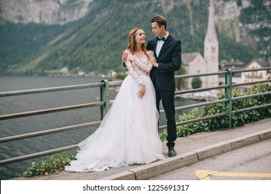 A beautiful wedding couple walks on a background old cathedral, lake and mountains in a fairy Austrian town, Hallstatt.