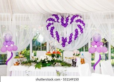 beautiful wedding decorations. Heart of white and purple balloons on a celebratory table.