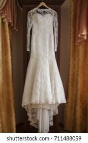 beautiful wedding dress   hanging  in room